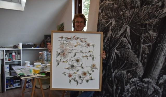 Marijke Wessel toont een kunstwerk in haar atelier. Haal het programma bij lokale bibliotheken en boekhandels of bekijk  www.kunsttoer.nl