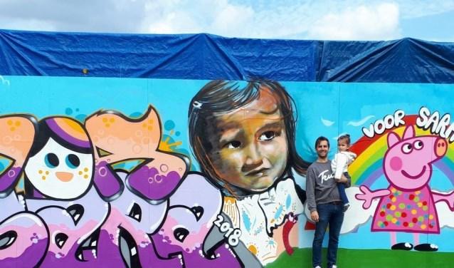 Bram en Sara voor de beschilderde muur van Vv Wieldrecht. (foto: pr)