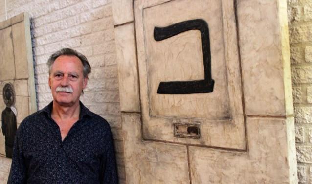 Jaap van Triest bij een van zijn werken, uit de Thora, Beth de Hebreeuwse letter  B. Een huis heeft drie muren en een deur. een huis dat voor iedereen open staat. Foto Dick Baas