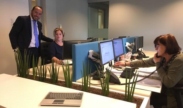Wethouder Oscar van Leeuwen bij de receptie, waar binnenkomende telefoontjes én WhatsApp-berichten worden afgehandeld.