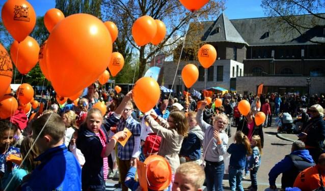 Kinderen laten traditiegetrouw ballonnen op tijdens Koningsdag.