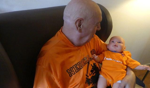Oranjefan Jan Bont maakt kennis met poppenkind, die voor de gelegenheid speciaal in het Oranje was gekleed