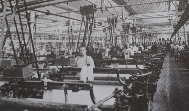 Een foto van arbeiders in een textielfabriek rond 1910.