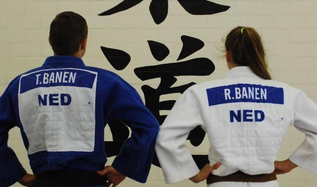 Broer en zus aanschouwen de Japanse tekens voor judo.