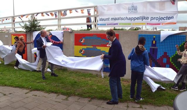 Wethouder Frans Hoogendijk (links) en Marja Tiemens (rechts) onthullen de puzzels aan de betonnen muur aan de Galgkade (Foto Frans Assenberg).