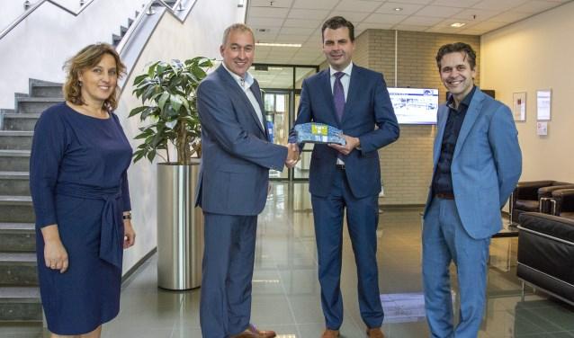 Wethouder Berend de Vries overhandigt een 'Benkske' aan Erik de Jonge CEO van Helvoet. (Jeroen Molenschot, Development manager en Caroline Bolder, HR Manager zijn ook aanwezig.