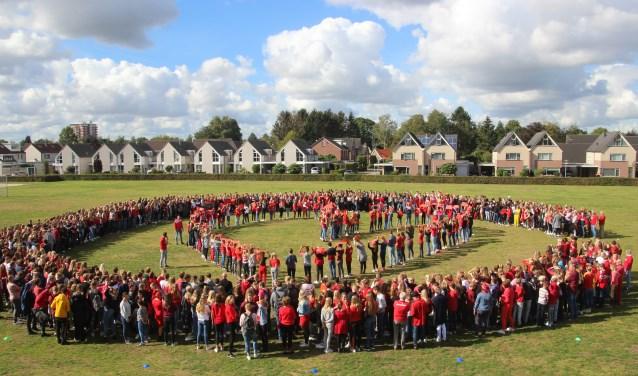 Alle leerlingen vormen samen een C, in het midden de brugklassers die in een hartvorm gegroepeerd zijn