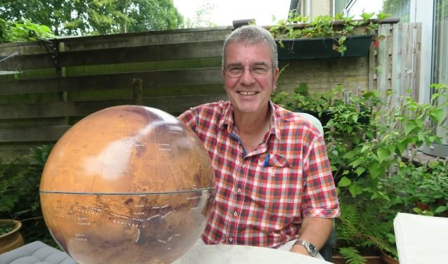 Rob Walrecht, autodidact sterrenkunde docent en eigenaar van zijn uitgeverij, bij een model van de rode planeet (foto: Marian Vreugdenhil)