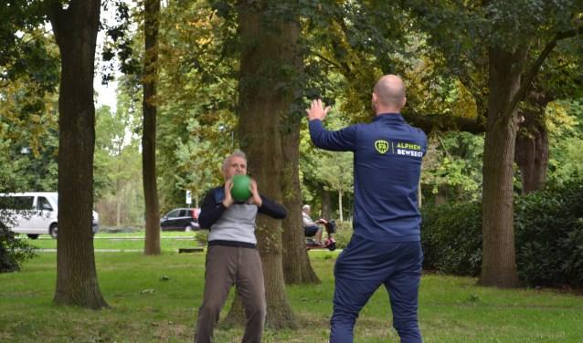 Op het grasveld achter het  Open Venster. Abdul doet balansoefeningen op de bal onder begeleiding van buurtsportcoaches Ton Bouman (links) en Robbin Hielkema (rechts).