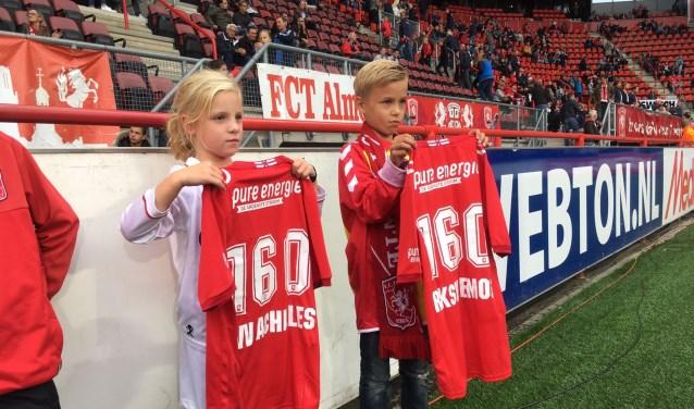 Maaike Egberink van EMOS en Lars van der Steeg van Achilles tonen hoeveel leden de wedstrijd tegen TOP Oss bezochten.