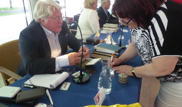 Taxateur Remy Gerritsen bekijkt de objecten die José uit Arnhem heeft meegebracht. (foto: Marnix ten Brinke)