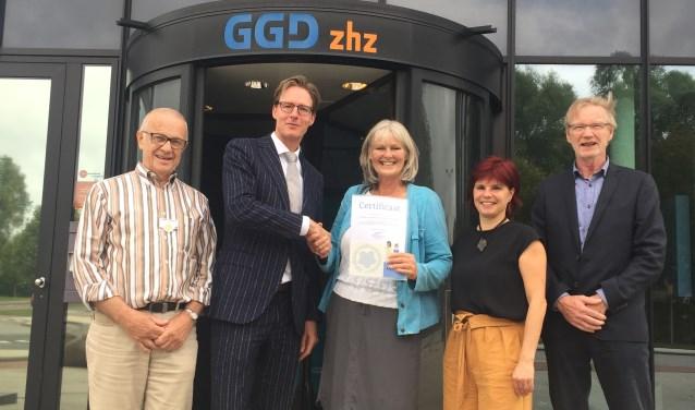 Aly Dassen, voorzitter afdeling Drechtsteden, Alblasserwaard en Vijfheerenlanden van Alzheimer Nederland, overhandigdehet certificaat 'dementievriendelijk' aan de GGD ZHZ.