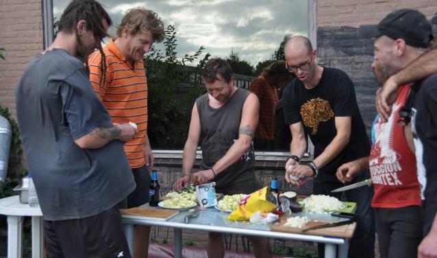 De bewoners van voormalige autoshowroom Hessing bereiden hun wekelijkse eetcafé-maaltijd. FOTO: Julie Houben