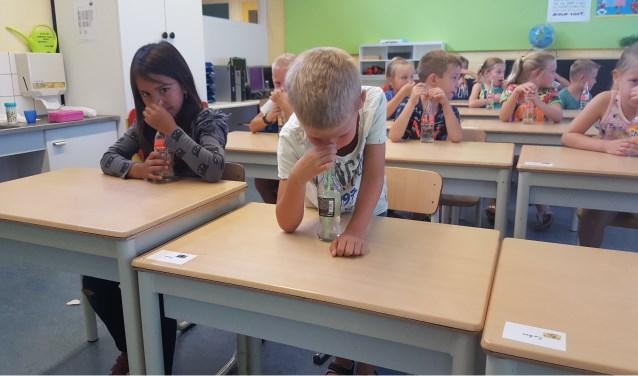 Leerlingen maken muziek met een rietje en een flesje water