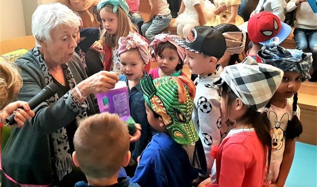 Juf Monique van Lieshout krijgt bij haar afscheid allerlei schoonmaakmiddelen. Haar kinderen dragen voor de gelegenheid een poetsdoek.