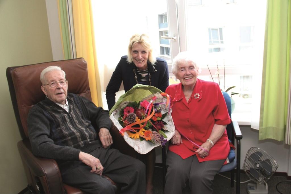 Locoburgemeester Ineke Knuiman wordt geflankeerd door het briljanten paar Mia (95) en Theo van Alst (92). Een mooie bos bloemen viel hen ten deel.