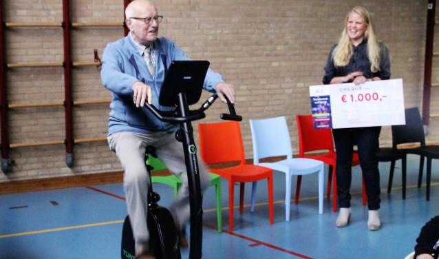 Henk van den Brink kon alleen nog maar fietsen. Voor de virtuele tocht door Amsterdam moest het scherm nog aangesloten worden. BCE-adviseur Maxine Hilhorst met de cheque kijkt toe. Foto Dick Baas