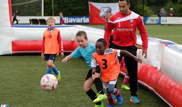De FC Utrecht trainer begeleidt de kinderen bij een partijvorm.