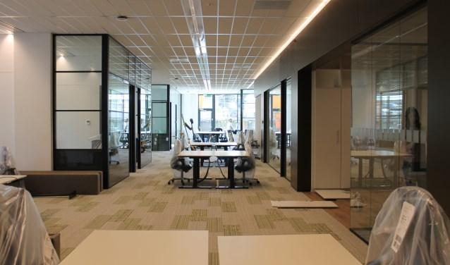 Het werkgebied van de gemeentelijke ambtenaren met flexplekken en stilteruimtes links en rechts achter de glazen wanden.