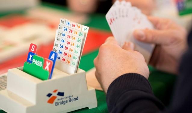 biedbakje en een hand met kaarten