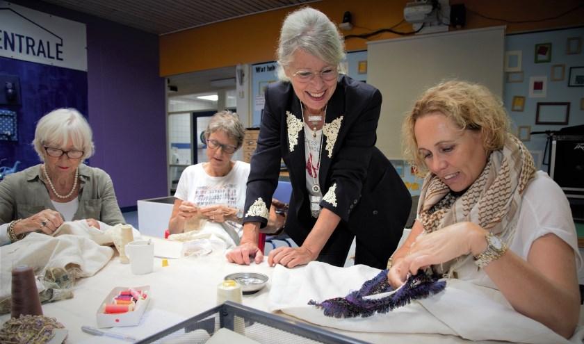 Enthousiaste naaisters helpen designer Franka van de Ven bij het met de hand appliceren van antieke Franse linnen hemden. (Foto: Bernadet de Prins)