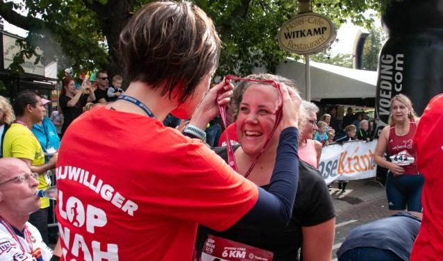 Deelneemster 6 km neemt medaille in ontvangst van een vrijwilliger