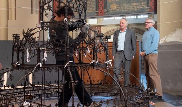 De kaarsenkroon wordt weer op zijn plek gebracht onder toeziend oog van Herman Krans (links) en Johan Oosterman. (Foto: Willem Feith)