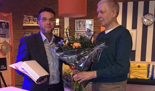 Voorzitter René Gelderman (links) huldigt Gerard Hopster voor zijn vijftigjarig jubileum.