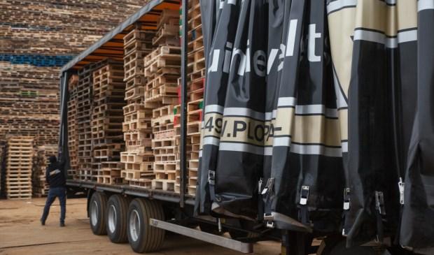 Pallets werden met vrachtwagens aangevoerd.