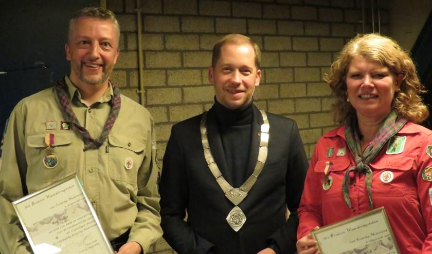 Burgemeester Rozendaal overhandigde het speldje en de oorkonde aan de twee vrijwilligers.