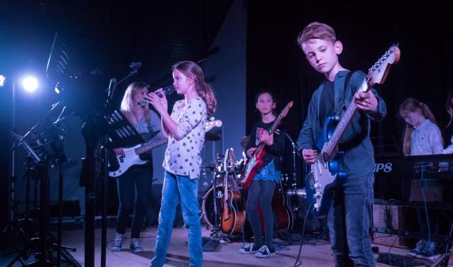 De kids maken kennis met elektrisch gitaar, basgitaar, drums, keyboards en zang.