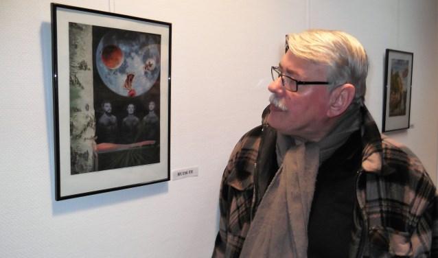 Cock Scheerens, peinzend bij een van zijn collages op de tentoonstelling in De Fonkel. Foto: Idor van Duppen.