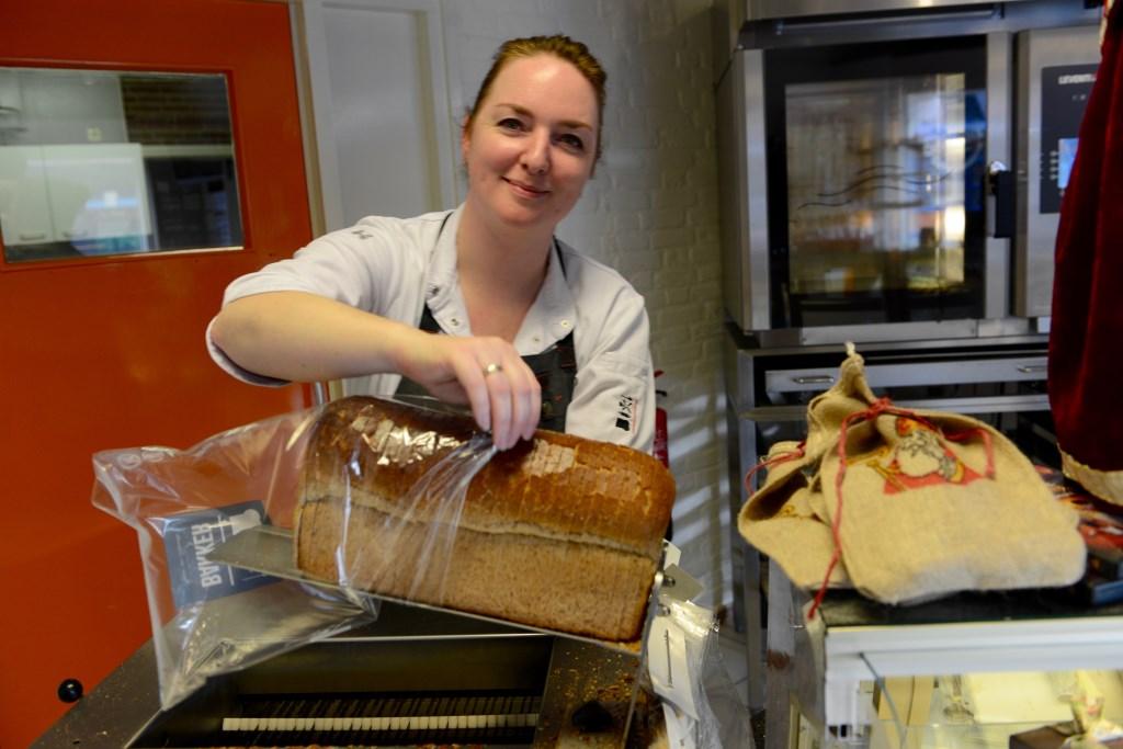 De dagelijkse klanten maken graag een praatje met Joke van Nieuwaal in de bakkerswinkel van de familie Bakker.  © Persgroep