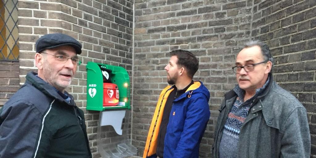 Willy Bergervoet, Stefan Ketelaar en Rene Bouwmeister bij het AED-apparaat dat aan de St. Martinuskerk is bevestigd