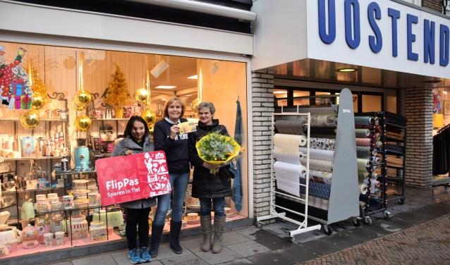 Diana Timisela (rechts) en haar dochter Betty (links) nemen de FlipPas maandprijs in ontvangst ter waarde van 500 euro, uitgereikt door Ingrid Oostendorp (midden). De bloemen zijn ter beschikking gesteld door Meeuwsen Bloemen.