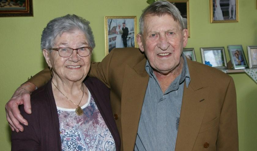 Corry en Bertus Bollen werden verrast door een bezoekje van de burgemeester die bloemen en een taart meenam.