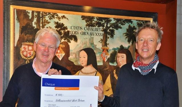 Bouwe Metz (links) overhandigt een cheque aan voorzitter Ruud van den Bos.