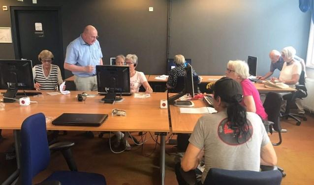 """Tijdens Klik & Tik in de Bibliotheek krijgen cursisten begeleiding van twee vrijwilligers. In Goirle zijn dat Arie en Jan. """"We blijven geduldig, hoe vaak een deelnemer ook dezelfde vraag stelt."""" foto: Yolanda van Leest"""