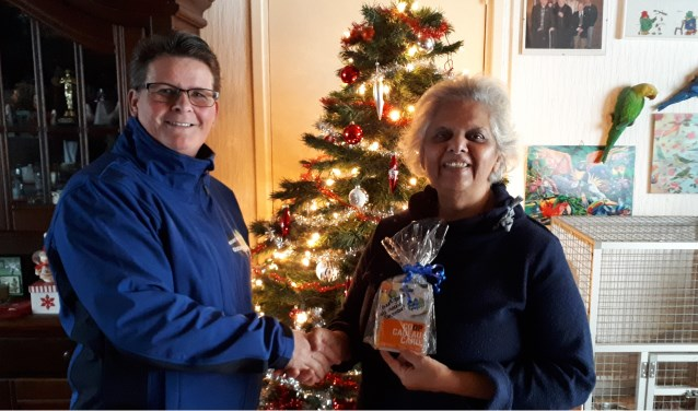 Patricia Couwenberg, voorzitter van Buurt Bestuurt Oudheusden, feliciteert de buurtbewoner van de maand december Bea van Spijk.