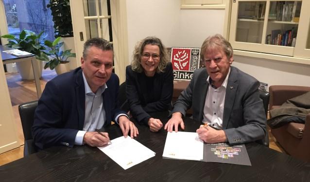 Wim van Ginkel (links) en René van Holsteijn (rechts) tekenen onder toeziend oog van Nancy van der Vin de overeenkomst tussen Rosa Novum en IW4