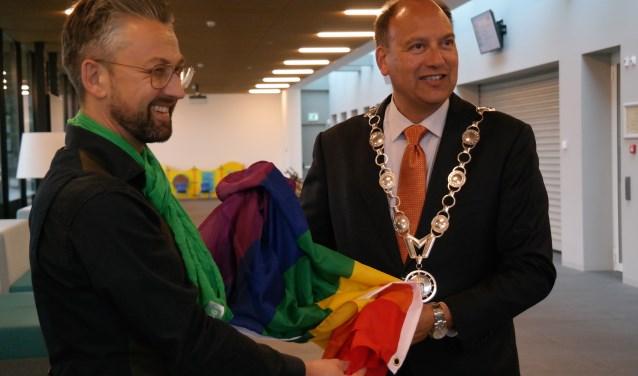 Ferry van Dijken overhandigt de regenboogvlag aan burgemeester Peter de Baat. (foto: PR)