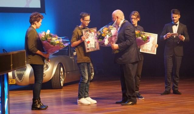 Frans Backhuijs reikt de oorkonde en bloemen uit aan Matthijs Hagen. Links staat Laura Hulzebos en rechts Sanne Berg. (Naomi Wijling)