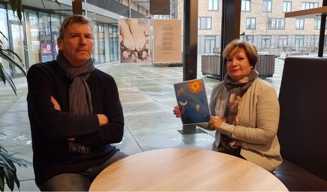 Arie van Driel en Cora van der Lee met een kopie van de schilderijen, waarbij ze een gedicht hebben gemaakt.