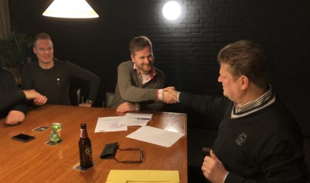 Voorzitter Karel van der Weert feliciteert Stijn Kistemaker met zijn verlenging. Assistent trainer Gerben Prins kijkt toe.