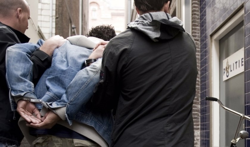 Man wordt geboeid afgevoerd. Foto: PR Politie
