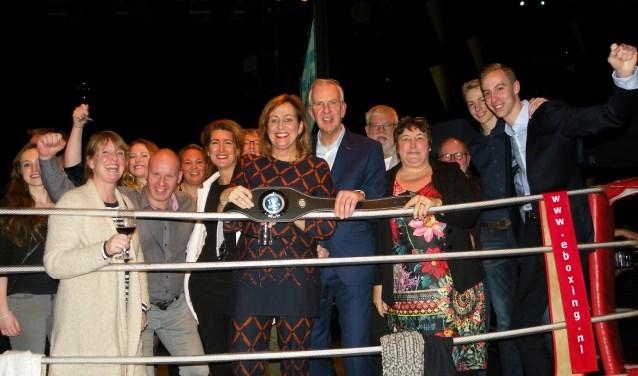 Monique en Jack Veldman (midden) vieren hun overwinning in de ring met familie en medewerkers.