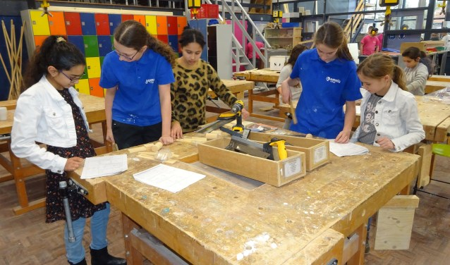 Derdeklassers leggen tien kinderen van de basisschool uit hoe zij iets moeten maken, vasthouden of assembleren. (Foto: Eline Lohman)