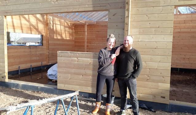 """Kim en Laurens voor hun houten huis in Toldijk. """"We verlangden naar meer regelmaat en rust in ons leven."""" (foto: Ceciel Bremer)"""