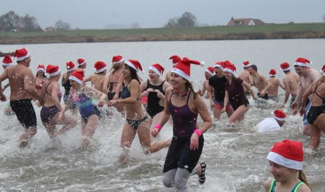 Het koude water van de Nederrijn werd door ongeveer honderd deelnemers getrotseerd. (Foto: Henk Jansen)