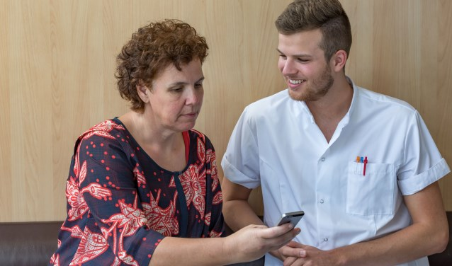Zorgverlener geeft patiënt instructie over BeterDichtbij app